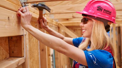 Woman in a hardhat hammering in a nail.