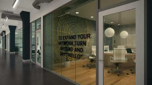 A meeting room with wood floor as seen through its glass wall and door from the hallway.