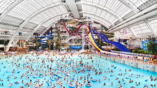 Large waterpark building with people swimming in water.