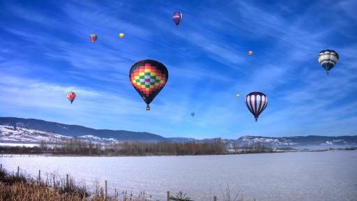 10 hot air balloons flying in a brilliant blue winter sky.