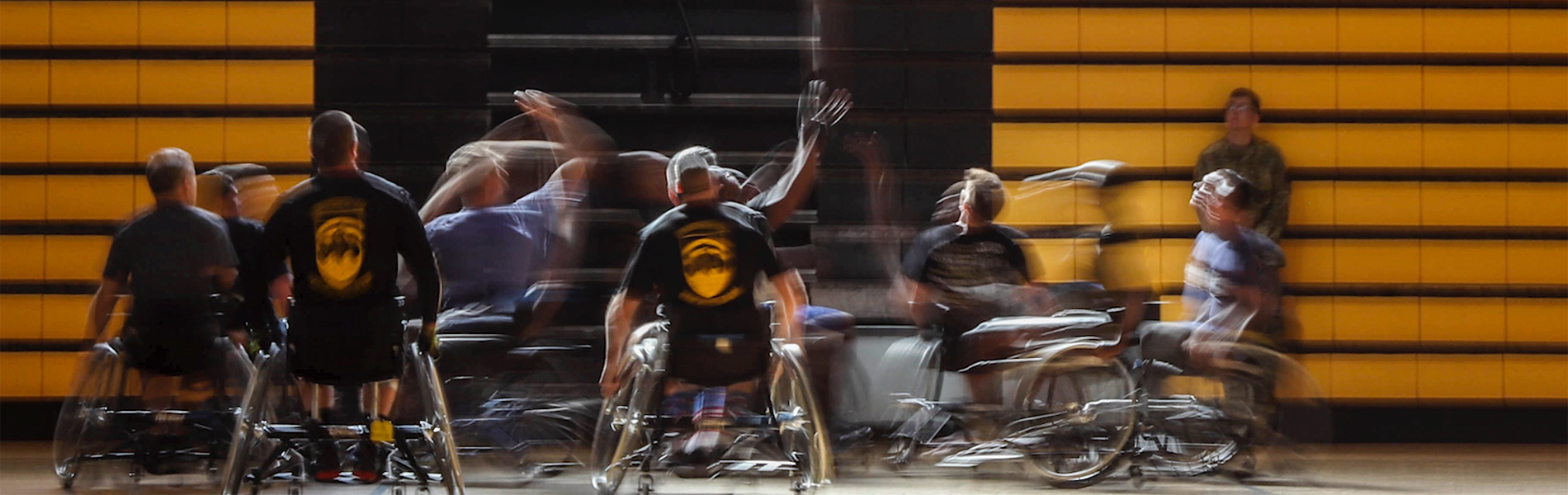 Group of men in wheelchairs playing basketball in a gym.