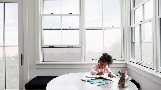 Child coloring on a table beside a large Pella Window