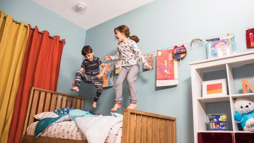 Kids jumping on bed with First Alert Onelink Safe & Sound product on ceiling.