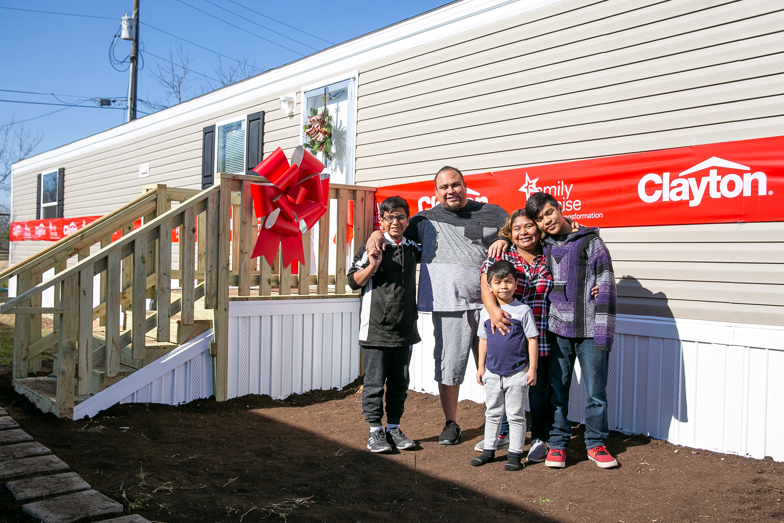 The De Paz family poses in front of their brand-new home.