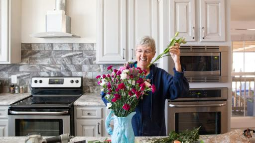 Woman putting flowers in a vase, in her new kitchen.