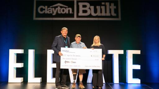 Three people on a stage holding a giant check.