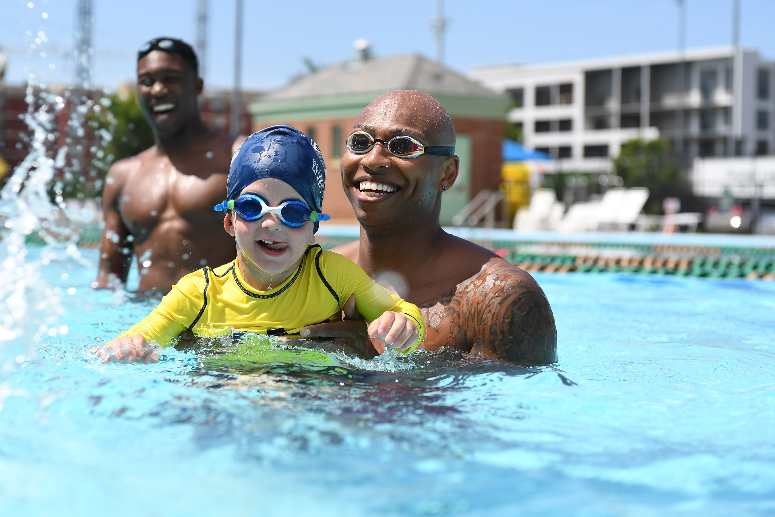PHOTO CREDIT: © Mike Lewis / USA Swimming Foundation - A child is taught to swim by USA Swimming Foundation ambassador and Olympic gold medalist Cullen Jones along with Sports Illustrated Sports Kid of the Year, Reece Whitley as part of USA Swimming Foundation's Make a Splash initiative.