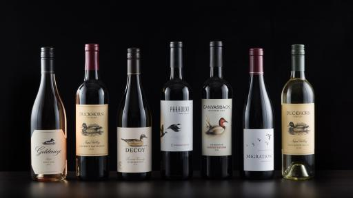 The Seven Masterful Wines standing lined up against a black background.