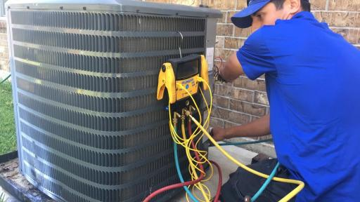 An installation technician from Fresh Air, Inc., in Houston installs a new Carrier air conditioner at a Habitat for Humanity home.