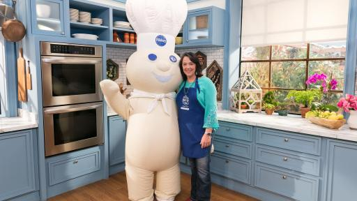 Amy Nelson and the Pillsbury Doughboy standing in a beautiful kitchen.