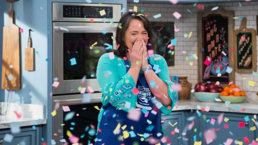 A very happy Amy Nelson stands behind a kitchen counter being showered with confetti.
