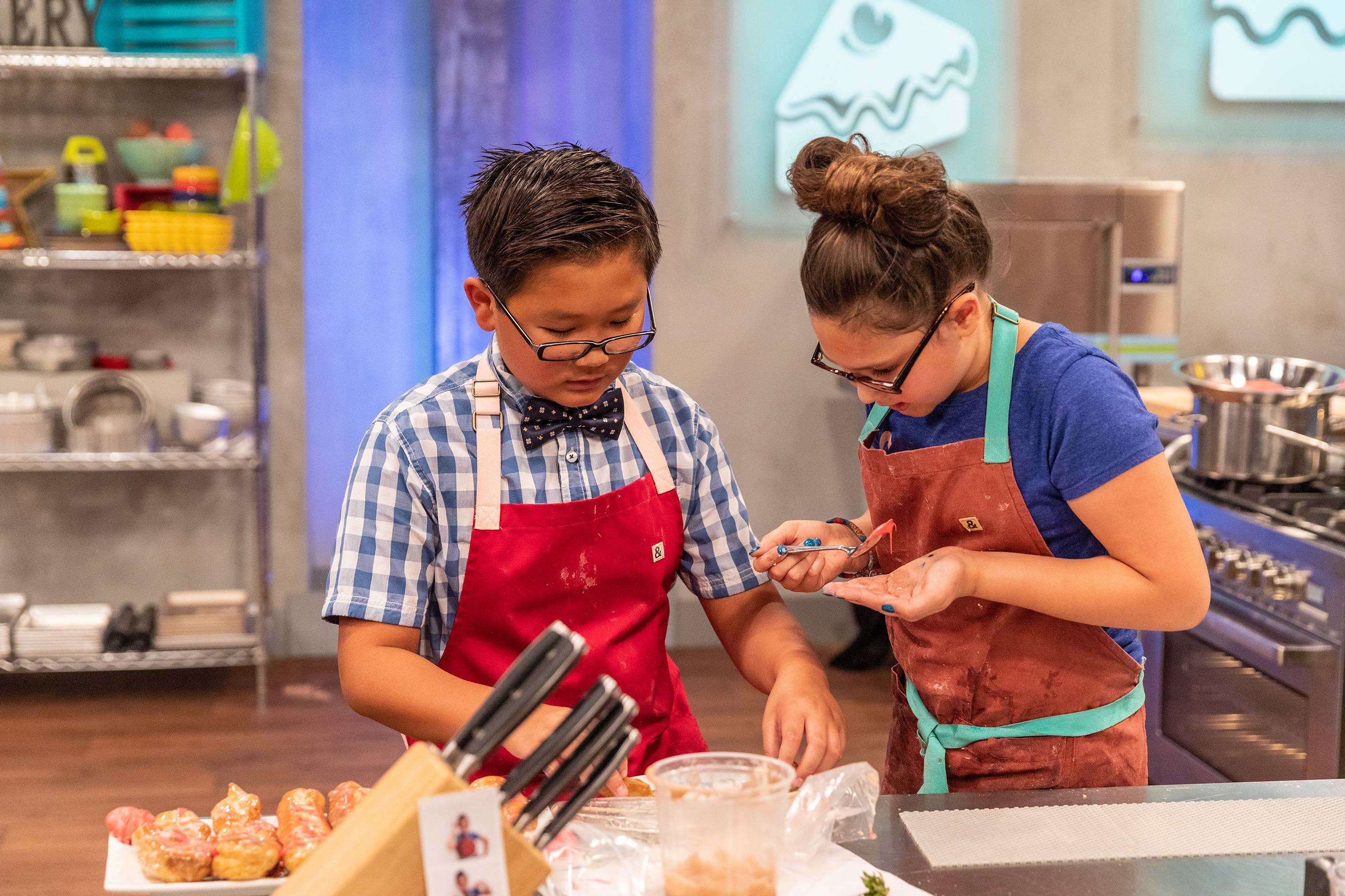 Matthew Azuma assists contestant Issi Neufeld on Food Network's Kids Baking Championship