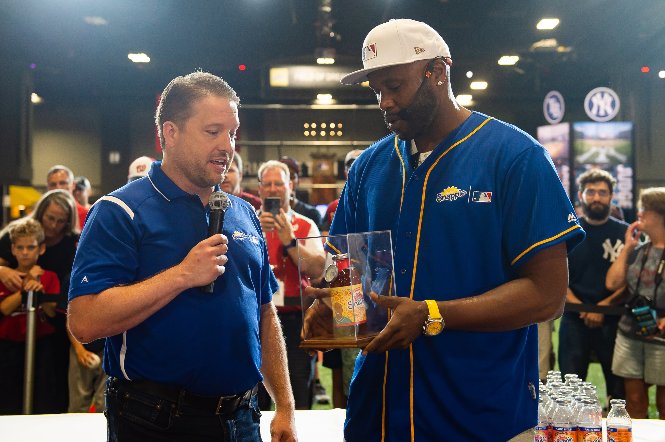 "Brent Chism from Snapple Brand Marketing presents Cliff Floyd with the ""Flip for Flavor"" trophy after winning the first-ever Snapple All-Star Bottle Flip Challenge at MLB FanFest. Cliff Floyd won after accurately flipping bottles onto fruit bases resembling a baseball diamond on Tuesday, July 17 in Washington."