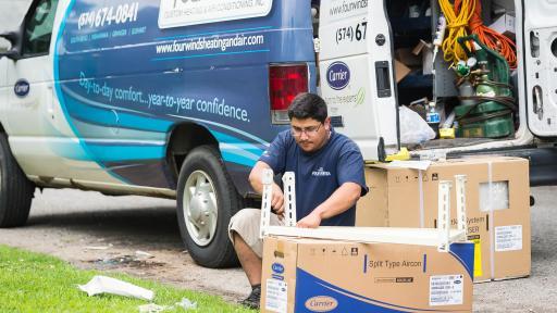 A technician unloading a van holding a box.