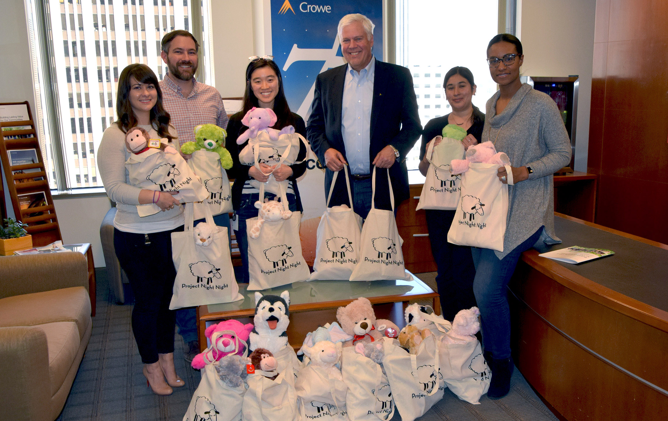 Crowe CEO Jim Powers joins volunteers from the firm's San Francisco office in preparing packages for Project Night Night.