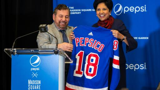 Three people holding up a PepsiCo jersey left to right: The Madison Square Garden Company Executive Chairman and CEO Jim Dolan; PepsiCo Chairman and CEO Indra Nooyi