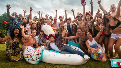 Man on a giant inflatable swan surrounded by friends at a pool party.