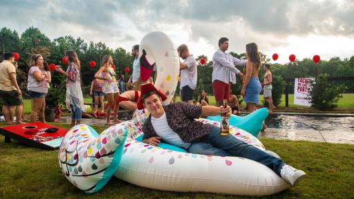 Man at a pool party lying on an inflatable swan with a bottle of captain morgan