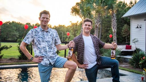 Adam Devine and Tyler Tills strike a pose with a bottle of rum on their knees in front of a pool.