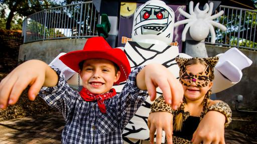 Boy dressed up as a cowboy and girl dressed up as a leopard standing in front of a Lego mummy