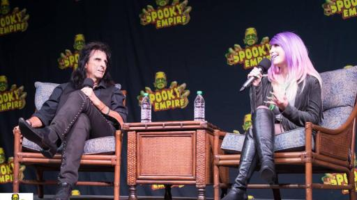 Alice Cooper on stage conversing with a woman with purple hair.