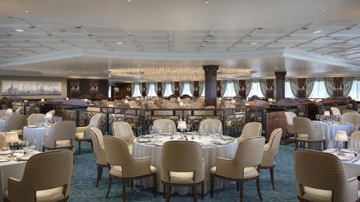 A large dining hall with chairs and tables that is the  The Grand Dining Room of the Regatta-Class ships