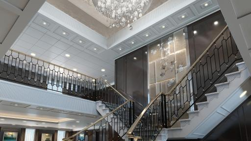 The Grand Staircase of the reimagined Regatta-Class ships with a giant chandelier in the ceiling.