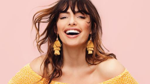 Magazine cover of a woman in yellow dress laughing.