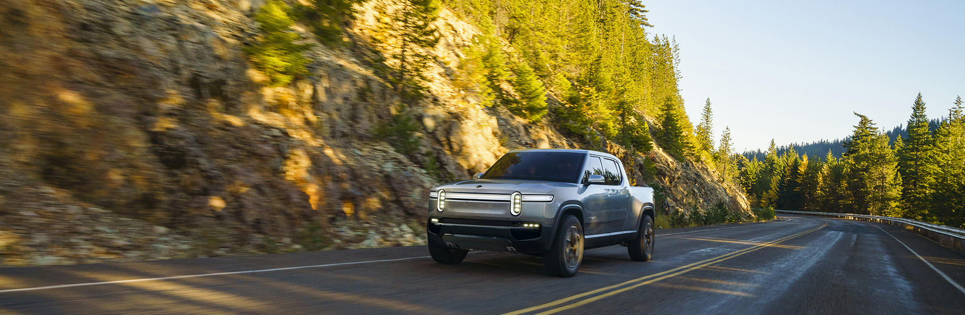Rivian Automotive all-electric pickup R1T driving down a wooded road.