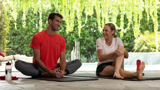 Michael Phelps and Mina Guli sitting on yoga mats and stretching