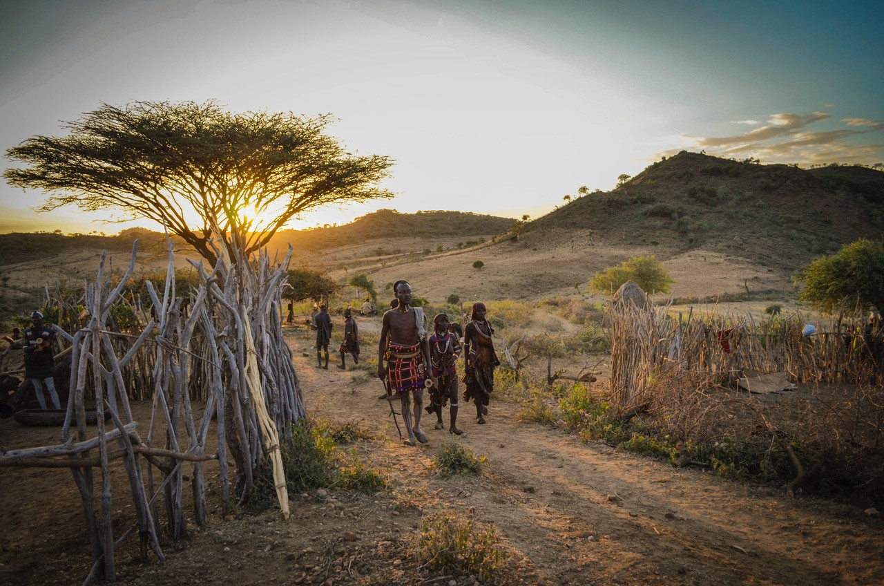 Tribesmen in the Omo Valley of Ethiopia in the golden glow of sunset. © G Adventures, Inc.