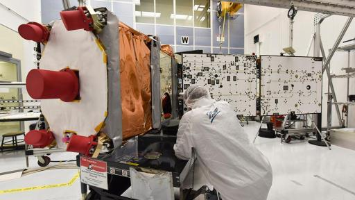 Ball Aerospace engineer dressed in a white smocks works on GPIM, a small satellite built for NASA, during solar array deployment