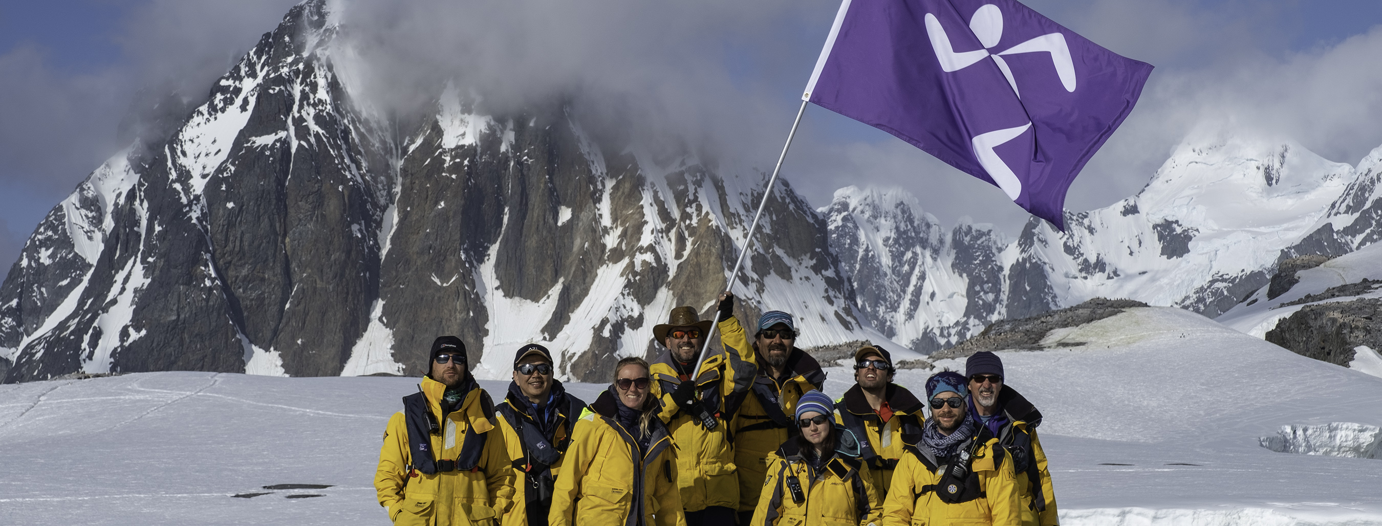 The Antarctic21 team guiding the Anytime Fitness flag