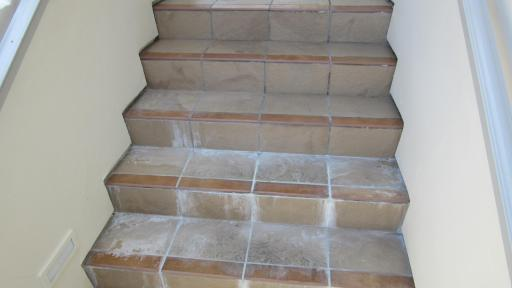 Efflorescence and damage at stair case caused by waterproofing failure.