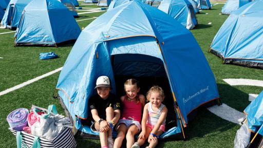 Three young children sitting in the front door of their blue tent.