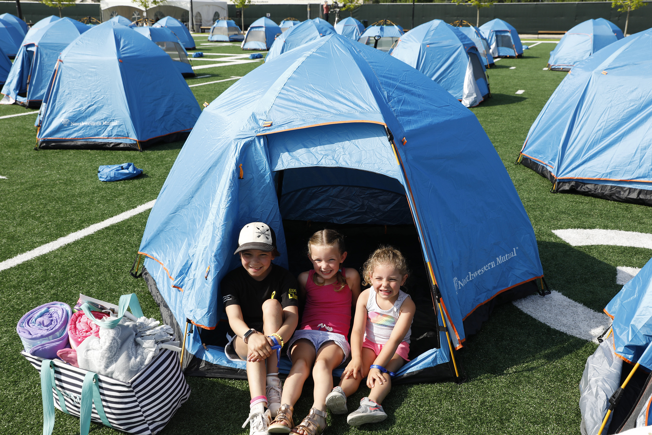 Northwestern Mutual's Ultimate Campout Fighting Childhood Cancer: Camp is an invaluable experience for children fighting cancer. Kids enjoy the sun after setting up  tents on the field at the Green Bay Packer's Titletown development.