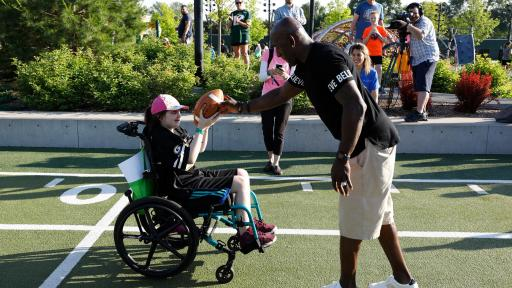 A man hands a football to a child in a wheelchair.