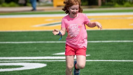 Young girl running on a field.