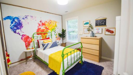 The children's bedroom, designed by Erin Marshall of Living Pretty on a Penny, aims to show kids how big and bright the world is with a colorful map and added adorable organization ideas like a reading nook made with bookshelves