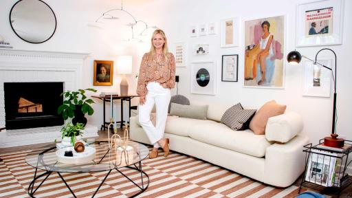 Emily Henderson, Author of STYLED, stands in the living room she designed with a personalized gallery wall and other lease-friendly ideas