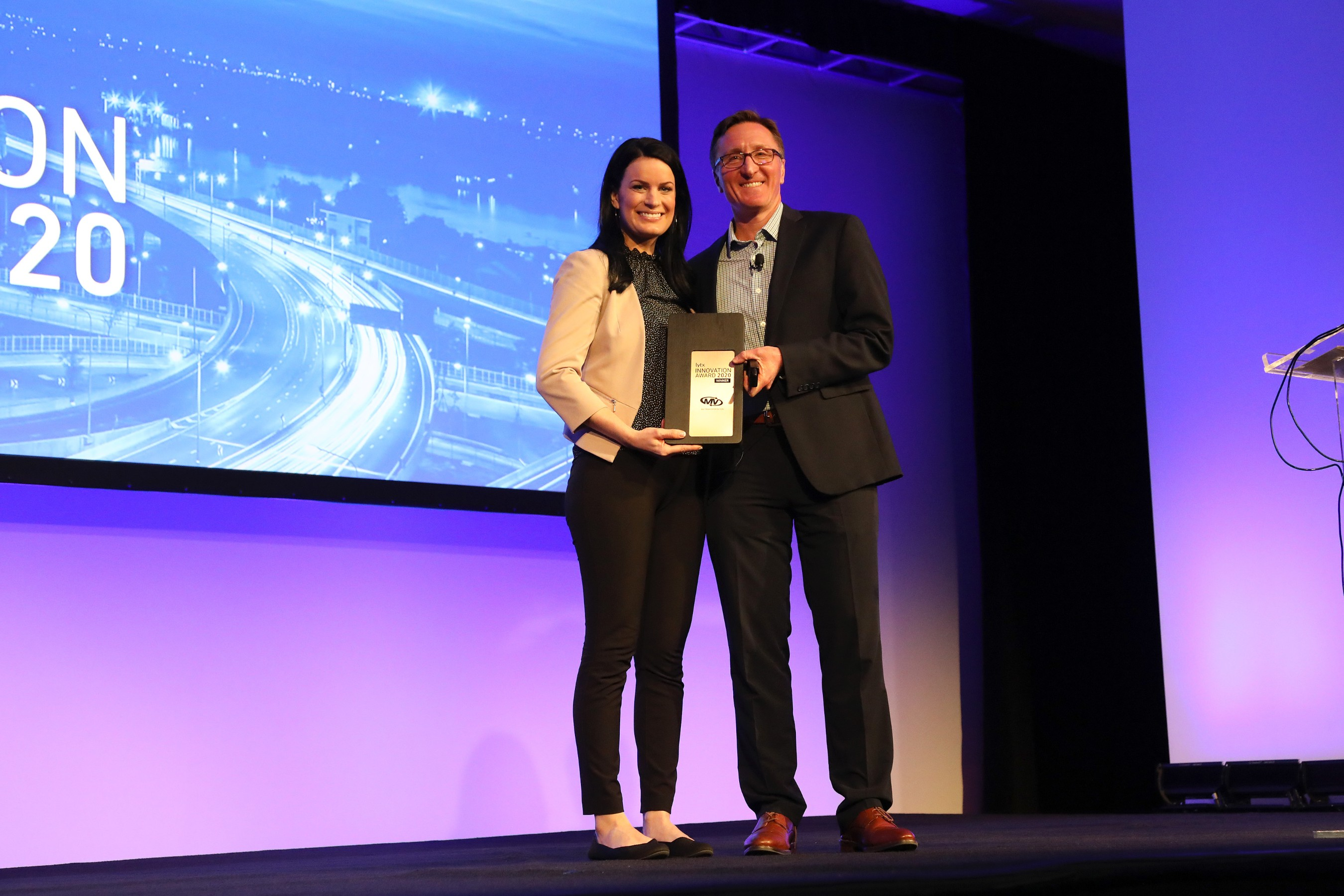 Stephanie Weber, Vice President of Safety Operations, MV Transportation, accepts Lytx inaugural 2020 Lytx Innovation Award from David Riordan, Lytx EVP and Chief Client Officer, at Lytx's User Group Conference. MV is a co-winner of the award, with Dycom Industries.