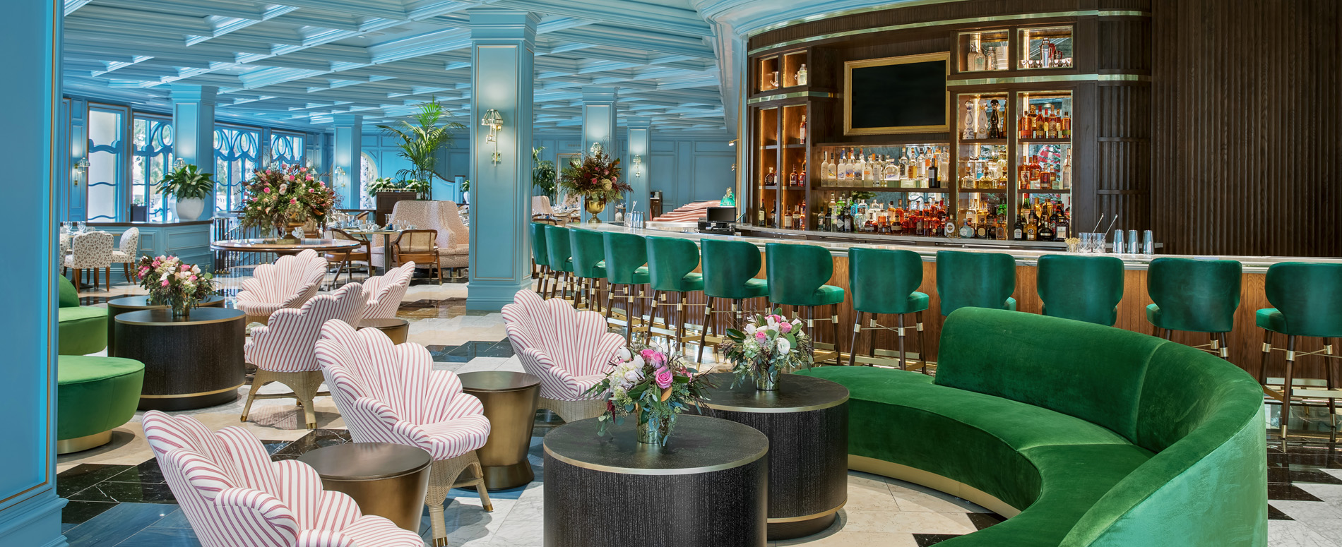 Interior shot of Sadelle's bar, with a teal blue ceiling and big green couches.