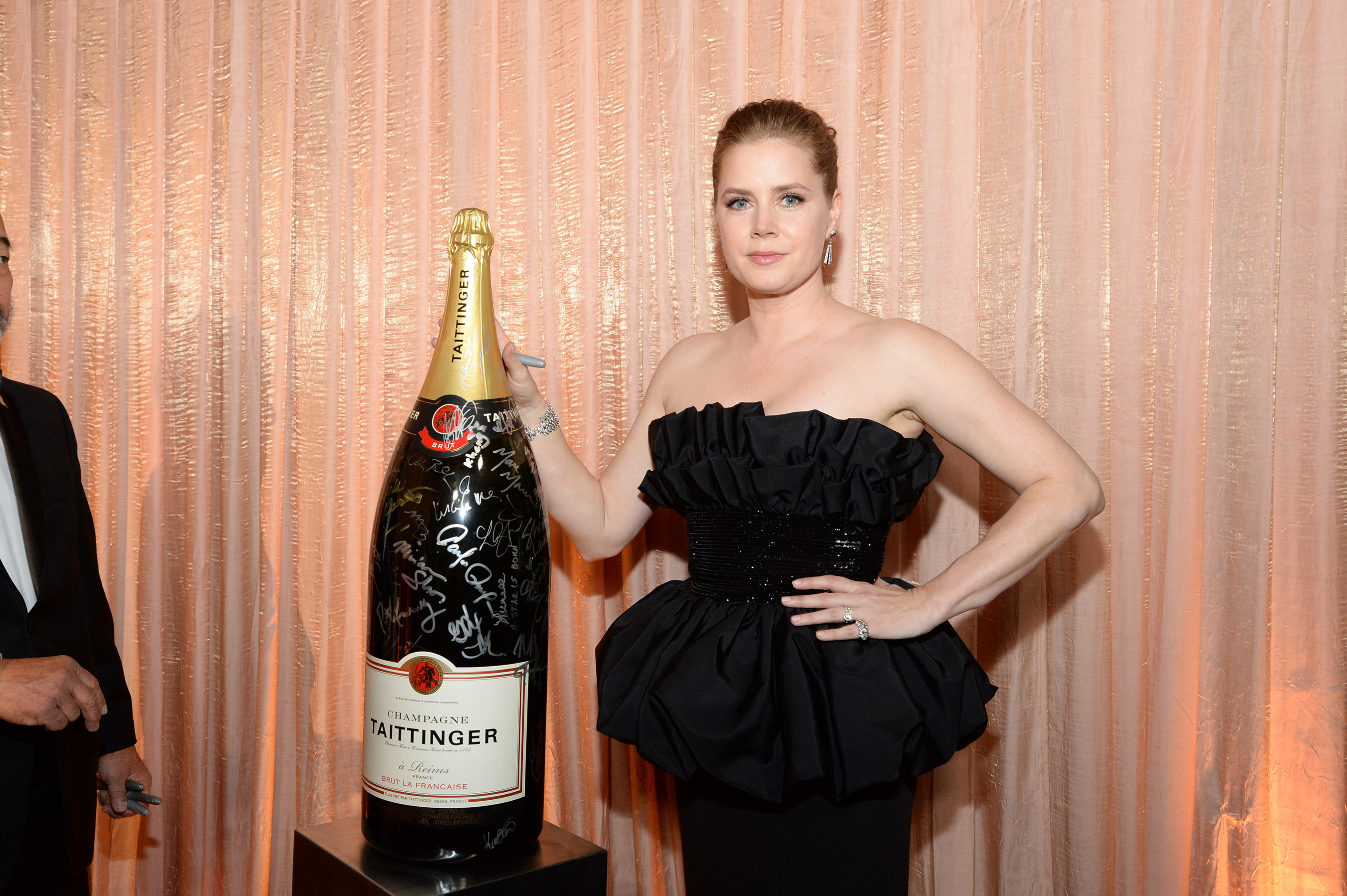 Amy Adams adds signature to Champagne Taittinger's bottle activation at the 25th Annual Screen Actors Guild Awards on January 27, 2019.