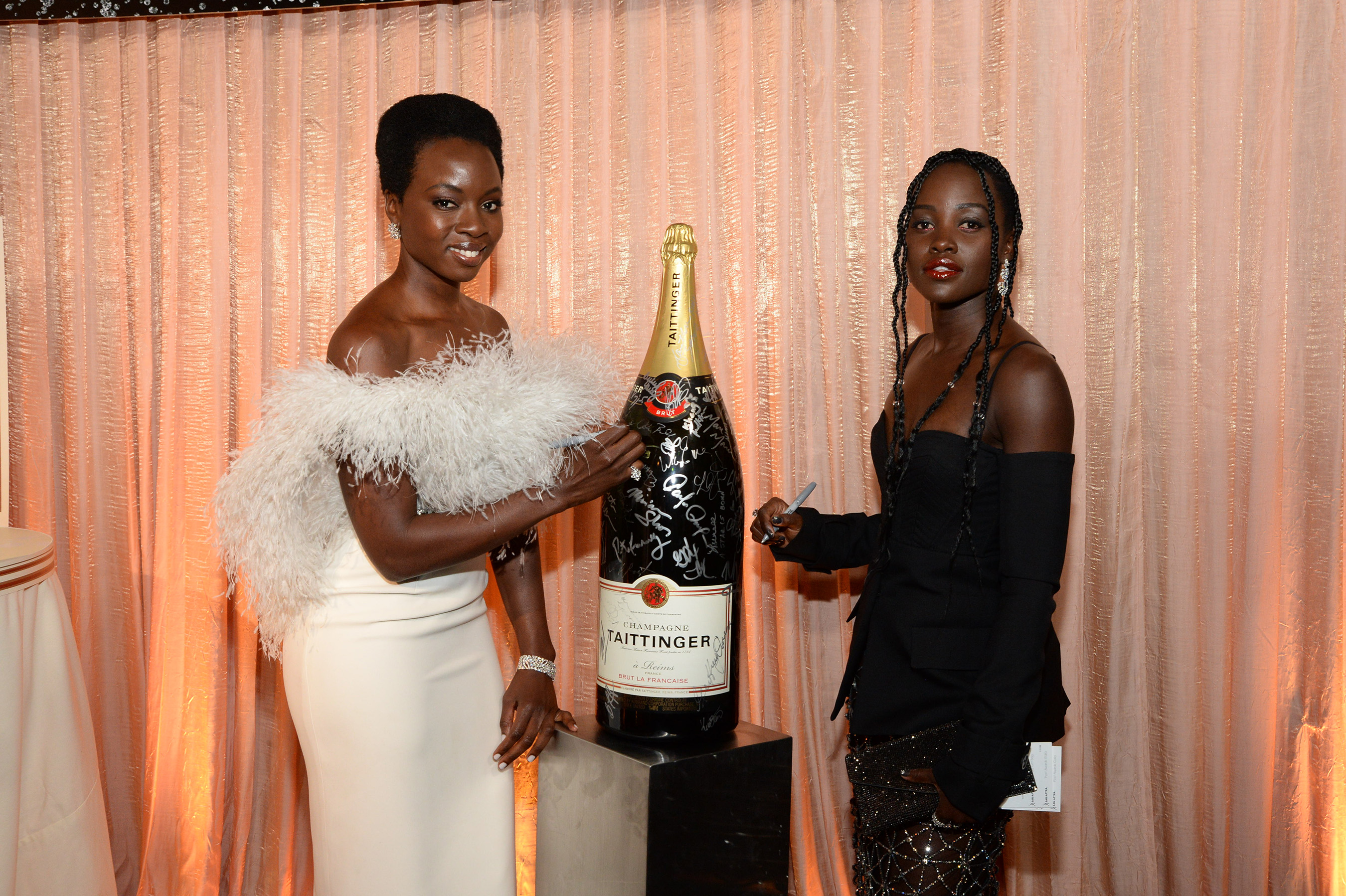 Danai Gurira and Lupita Nyong'o add their signatures to Champagne Taittinger's bottle activation at the 25th Annual Screen Actors Guild Awards on January 27, 2019.