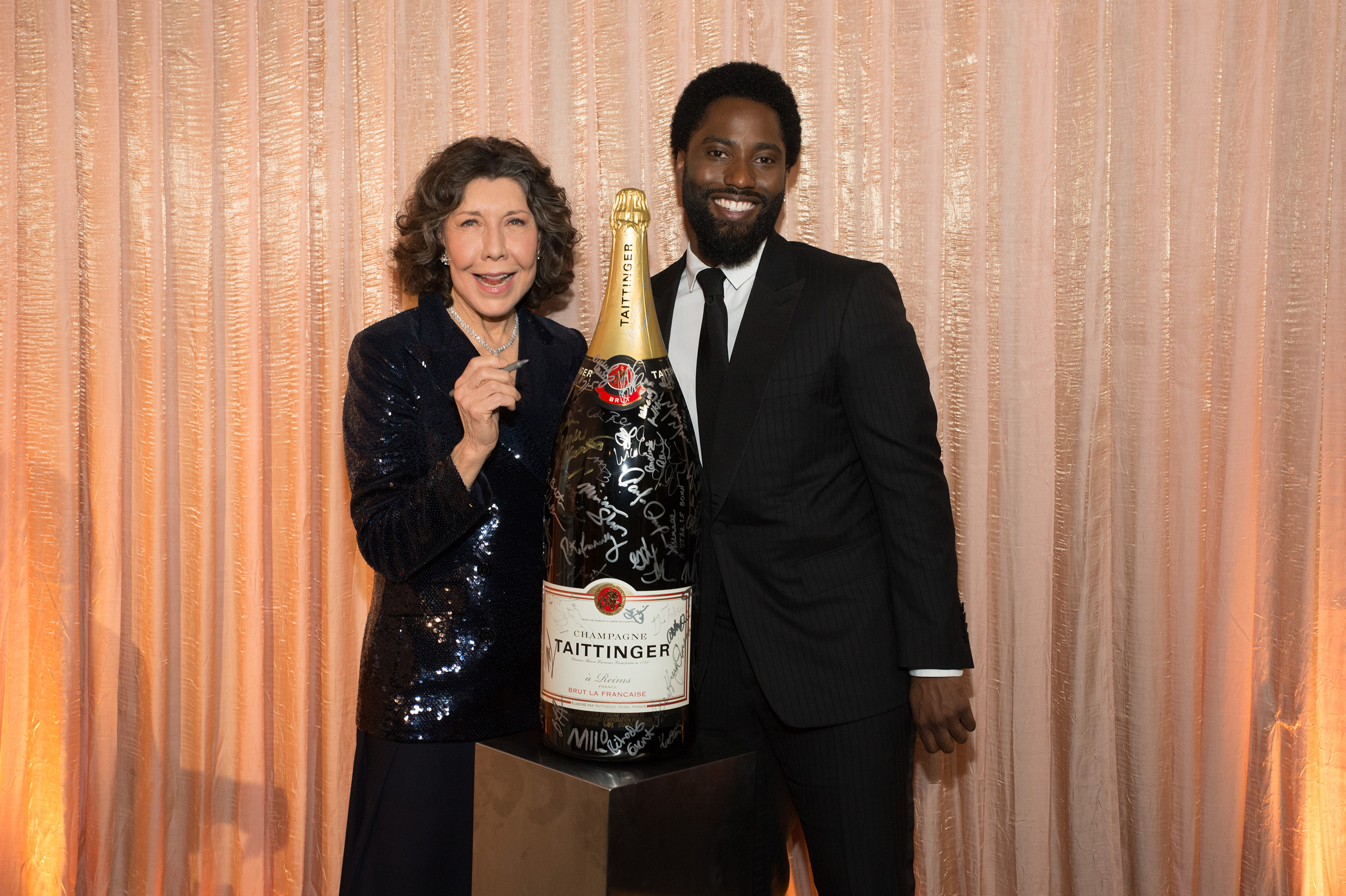John David Washington & Lily Tomlin add their signatures to Champagne Taittinger's bottle activation at the 25th Annual Screen Actors Guild Awards on January 27, 2019.