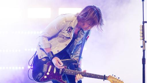 Keith Urban playing guitar on stage