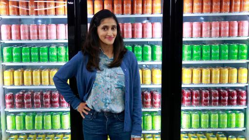 Aparna Nancherla standing in front of coolers of drinks