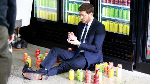 Michael Bublé sitting in front of coolers of drinks