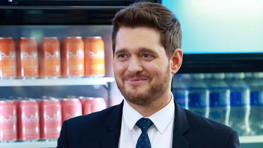 Michael Bublé standing in front of coolers of drinks.