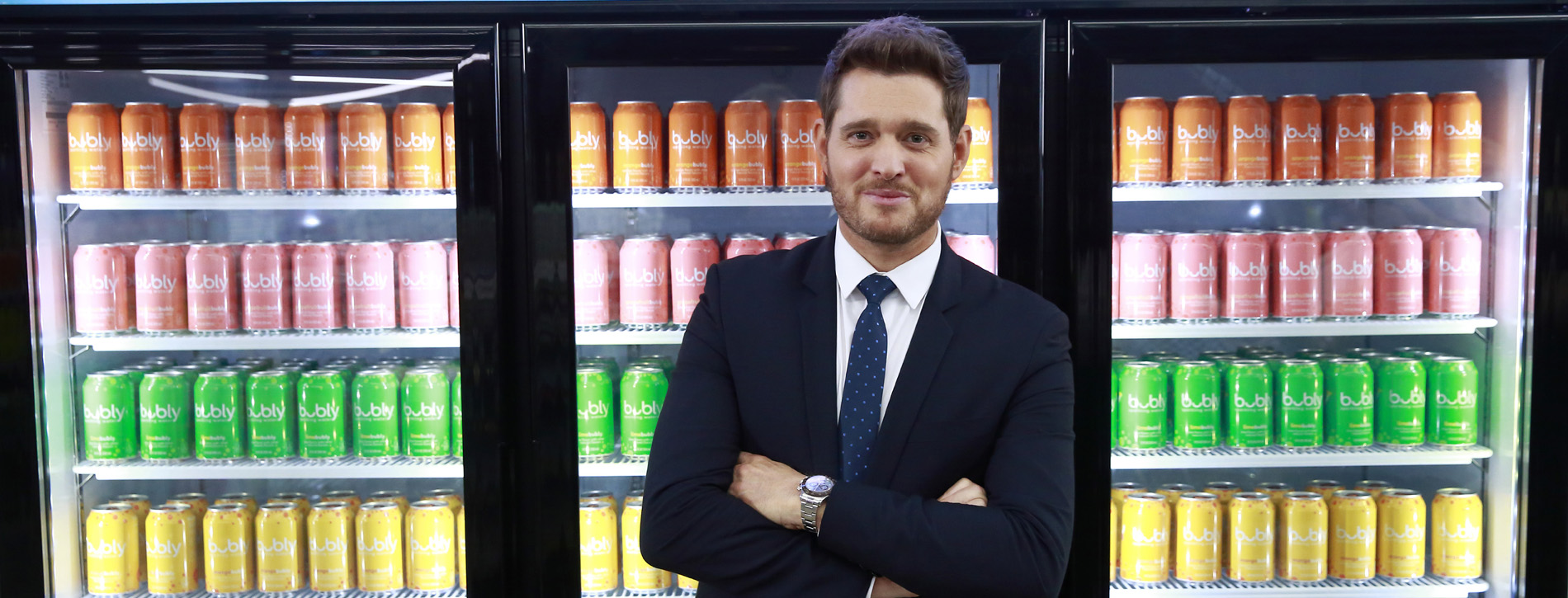Michael Bublé standing in front of coolers with Bubly water.